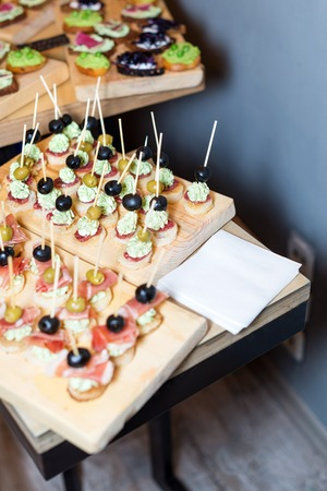 sample tray: Wooden tray of appetizers on pallet coffee table at banquet with jamon, butter cream and olives. Selective focus