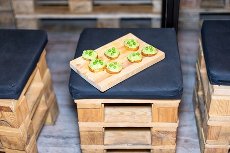 Wooden tray of appetizers on pallet coffee table at banquet