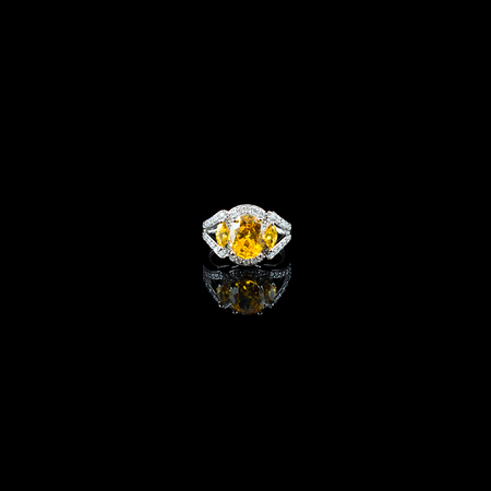 red stone: Silver or white gold ring with yellow gems and diamonds on black glass background