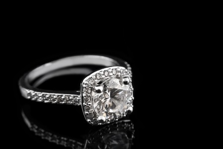 Luxury jewellery. White gold or silver engagement ring with diamonds closeup on black glass background. Selective focus