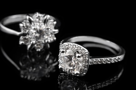Luxury jewellery. White gold or silver engagement rings with diamonds closeup on black glass background. Selective focus