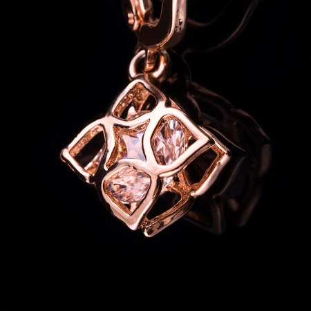 precious stone: Beautiful golden pendant with precious stone placed on black glass background. Macro photo