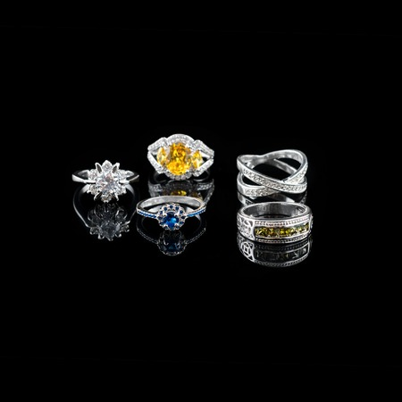 Collection of rings with colorful gems on black background Archivio Fotografico