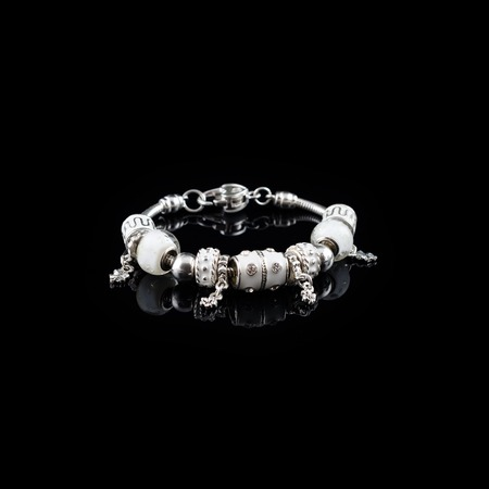 Pandora style silver bracelet with white charms isolated on black glass background