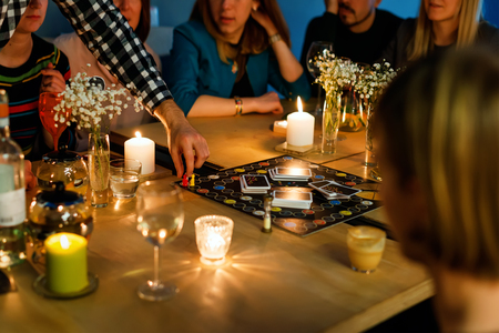 Group of people gathered to play Alias game. Young people hanging out together around a table during a party playing a game. Selective focus