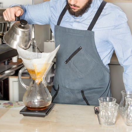 espreso: Barista making kemeks coffee. Man with a beard pours boiling water into the filter with ground coffee