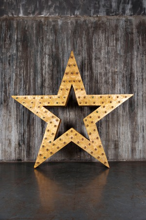 big star: Big star with illumination on it on the background of concrete wall. Installation for performance or design element in the loft