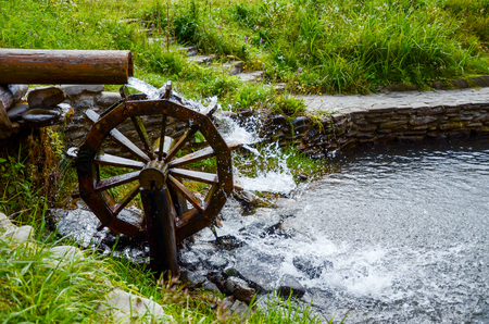 Working watermill wheel with falling waterin the village