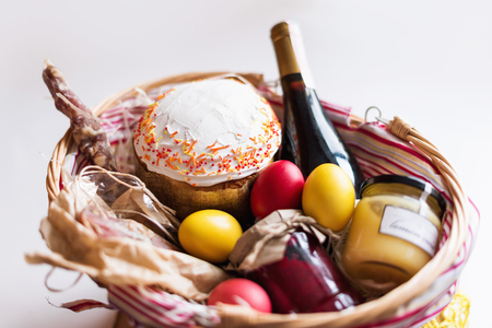Bunte Ostereier in einem Korb mit Kuchen, Rotwein, Hamon oder ruckartig und trocken geräucherter Wurst auf weißem Hintergrund