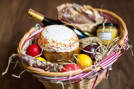 food basket: Colorful easter eggs in a basket with cake, red wine, hamon or jerky and dry smoked sausage on wooden background Stock Photo