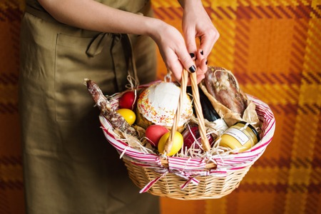 basket: Female hands holding easter basket with colorful easter eggs, cake, red wine, hamon or jerky and dry smoked sausage. Food gift set for celebrating Easter