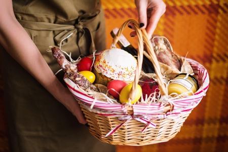 Weibliche Hände halten Ostern Korb mit bunten Ostereiern, Kuchen, Rotwein, Hamon oder ruckartig und trocken geräucherter Wurst. Lebensmittel-Geschenk-Set für Ostern feiern