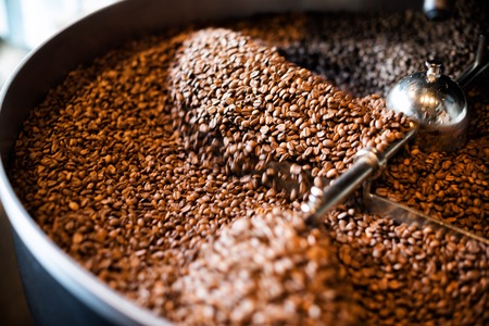Roaster: The freshly roasted coffee beans from a large coffee roaster in the cooling cylinder. Motion blur on the beans