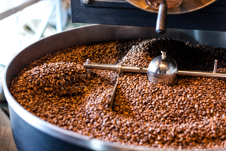 The freshly roasted coffee beans from a large coffee roaster in the cooling cylinder. Motion blur on the beans