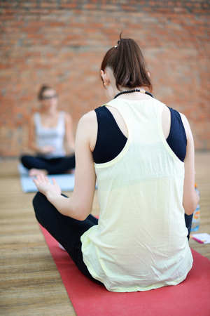 abductor: Young women do yoga indoors. Girl sitting in easy yoga pose with her yoga teacher and meditating. Selective focus
