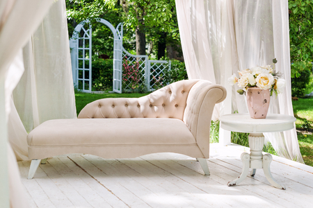 Summer garden gazebo with curtains and sofa for relaxation Stock Photo