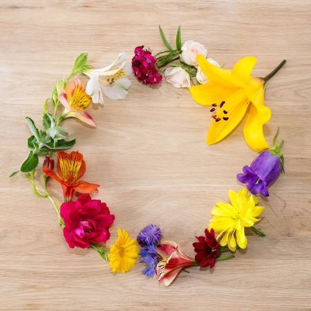 Frame made of different flowers on wooden background