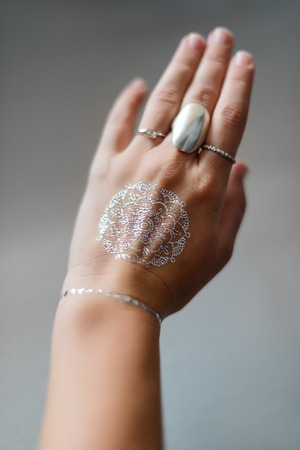 bracelet tattoo: Woman hand with silver jewelry and flash tattooes in indian style. Summer beach fashion. Selective focus