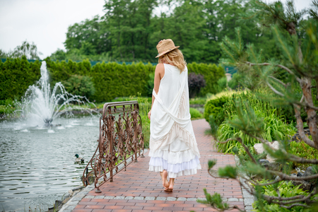 barefoot blonde: Happy young blonde woman walking barefoot in the park. Summer holidays lifestyle concept