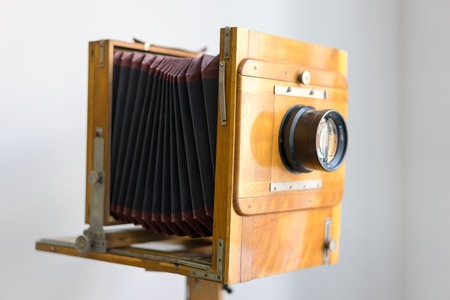 Vintage box camera with a wooden body standing near the window on white background