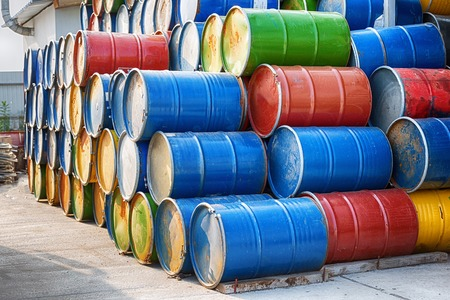 Colorful old industrial metal drum barrels stacked