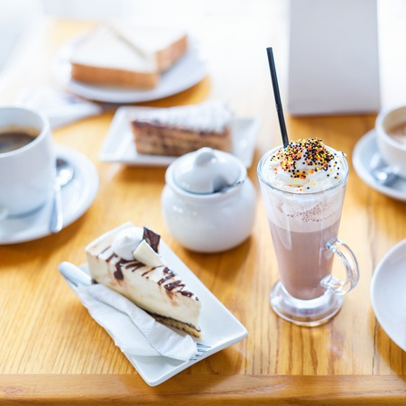 Breakfast or afternoon snack with creamy cappuccino and cake on wooden table
