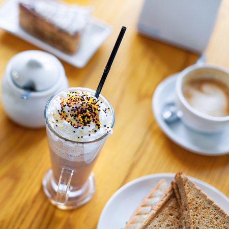 Breakfast or afternoon snack with creamy cappuccino, sandwich and cake on wooden table
