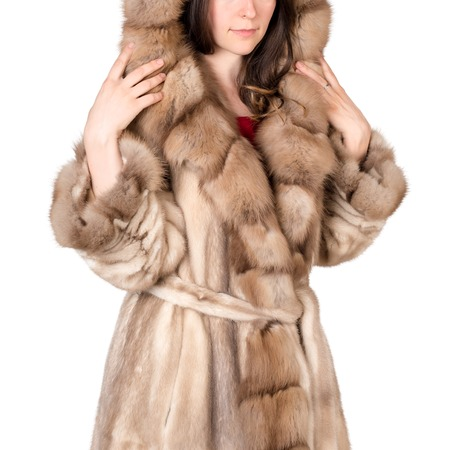 Young woman wearing fur coat on white background