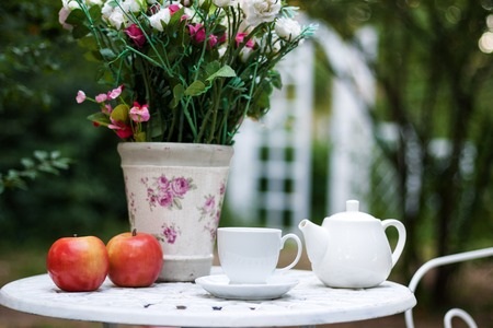 picnick: White porcelain set for tea or coffee on table in the garden over blur green nature background, shallow depth of field