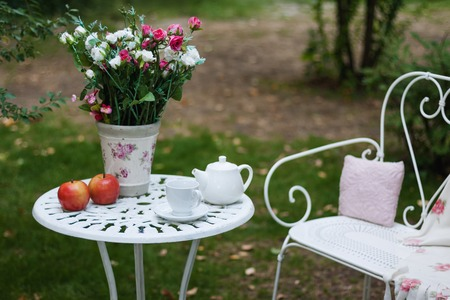 picnick: White porcelain set for tea or coffee on table in the garden over blur green nature background. Summer outdoor party setting Stock Photo