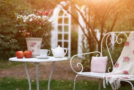 picnick: White porcelain set for tea or coffee on table in the garden over blur green nature background Stock Photo