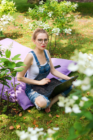 Freelancer working in the garden. Writing, surfing in the internet. Young woman relaxing and having fun in park area. Distance education, freelance concept