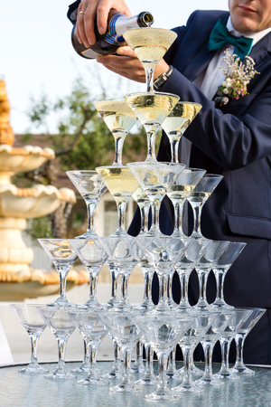 Groom filling a pyramid of glasses with champagne at outdoor garden in wedding ceremony