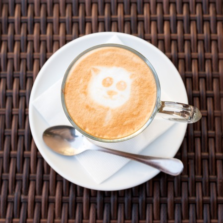 Cup of hot latte art coffee on wicker wooden table