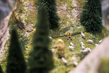 ovejitas: Gente miniatura: joven pastor lee un libro y ovejas caminando a su alrededor en la hierba verde del césped. foto macro, DOF Foto de archivo