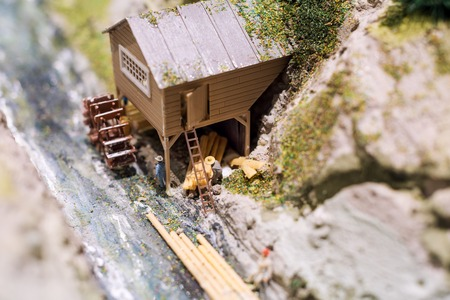 sawmill: Miniature people: workers on sawmill at the river. Macro photo, shallow DOF