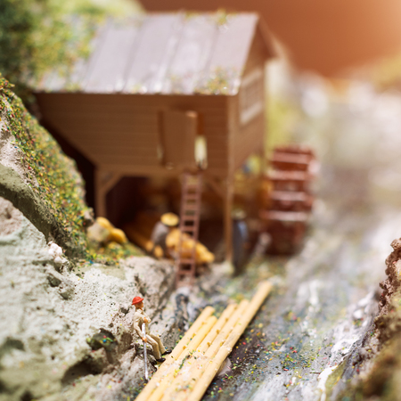 Miniature people: workers on sawmill at the river. Macro photo, shallow DOF