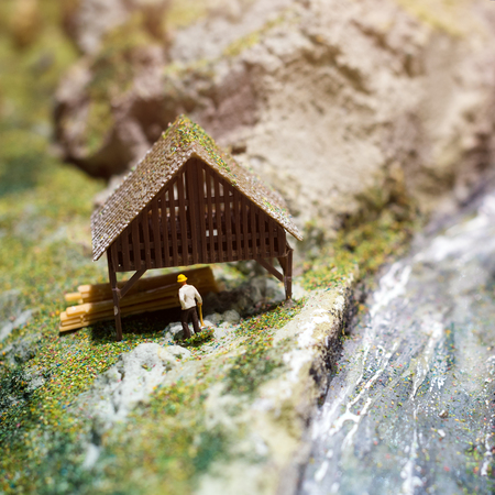 sawmill: Miniature people: worker on sawmill at the river. Macro photo, shallow DOF