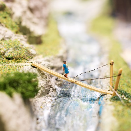 Miniature people: woman walking on the bridge. Macro photo, shallow DOF
