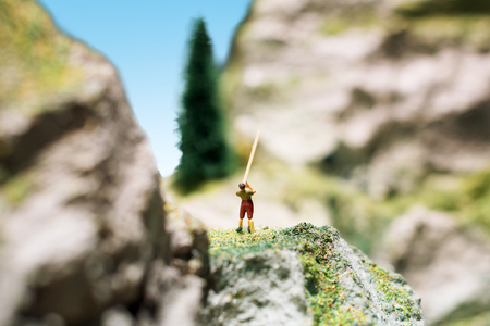 green military miniature: Miniature people: young man playing long trumpet in the mountains. Adventure, travel, tourism, hike and eco nature concept