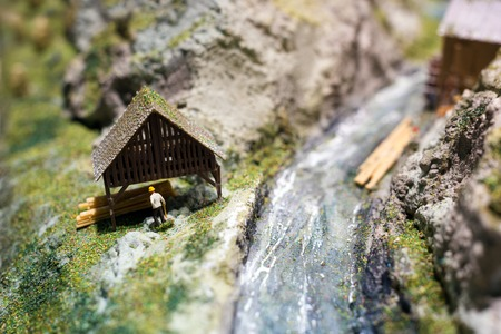 Miniature people: worker on sawmill at the river. Macro photo,