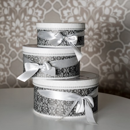 Three round celebration gift boxes with silver ribbon bows on white table. Stack of presents in luxury interior Stock Photo