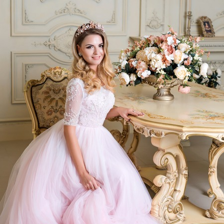 luxury apartment: Beautiful blonde woman wearing gorgeous dress and crystal crown posing in luxury classic apartment Stock Photo