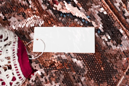 sequins: Epty white cloth tag on sequins fabric. Shopping or sale concept.