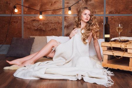 Femme nue enveloppée dans une couverture avec un verre de vin blanc. Belle fille blonde appréciant l'alcool. Soirée cosy des vacances d'hiver. Banque d'images - 68872696