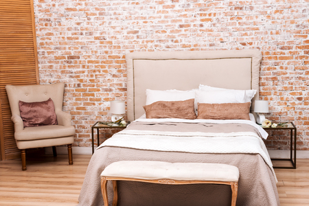 loft: Beautiful loft bedroom with bed and armchair near brick wall
