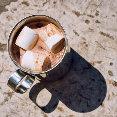 Metal touristic mug of cocoa with marshmallow on a stone background.