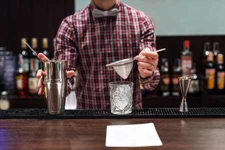 bartending: Barman show. Bartender is making cocktail at night club.