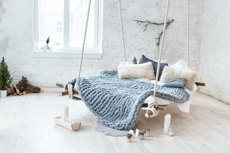 White loft interior in classic scandinavian style. Hanging bed suspended from the ceiling. Cozy large folded gray plaid, giant knit blanket, super chunky yarn, arm knitting. Trendy room design.