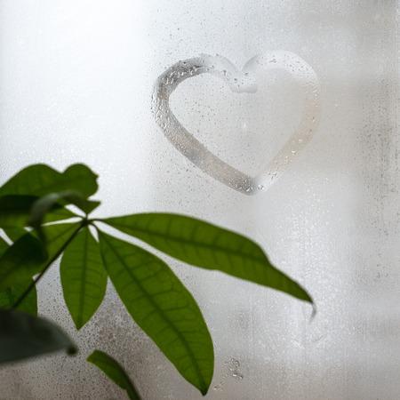 dearest: Inscription on the sweaty window glass, shape of heart. Love and romance symbol.
